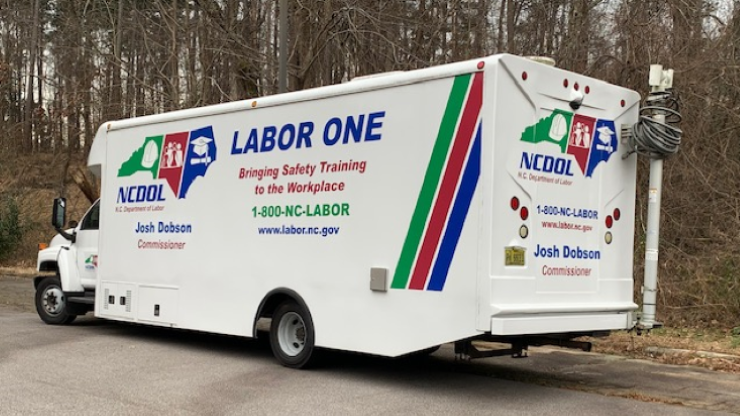 The Labor One Mobile Training Unit, a white truck with NCDOL contact information on it, is parked on concrete.