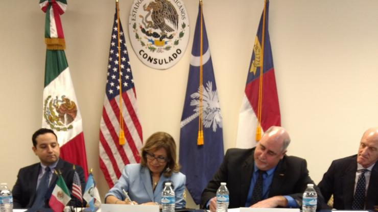 Commissioner Berry signs an alliance agreement with Mexican Consulate at a table with three other people