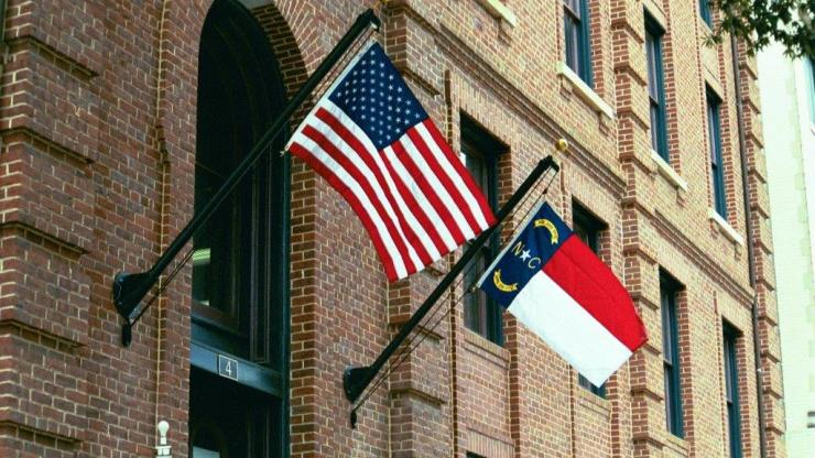 Red brick labor building with the USA and NC flags hanging in front of the entrance at 4 W Edenton Street