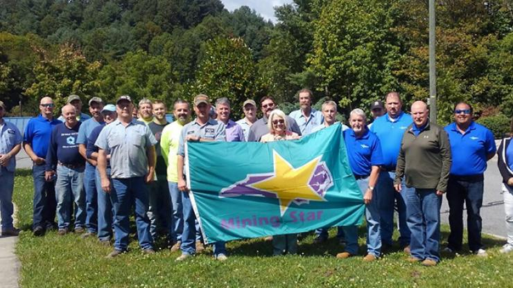 A group of people pose with Commissioner Berry while holding the Carolina Mining Star flag