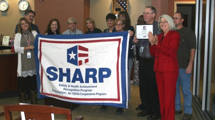 A group poses with Commissioner Berry at a SHARP ceremony while holding the SHARP flag