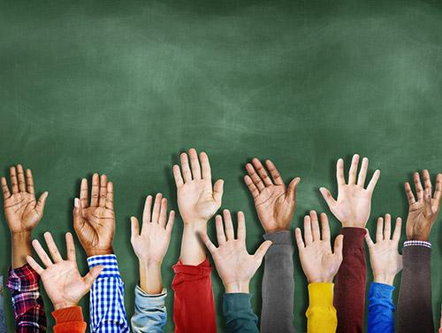 Raised children hands in front of chalkboard.