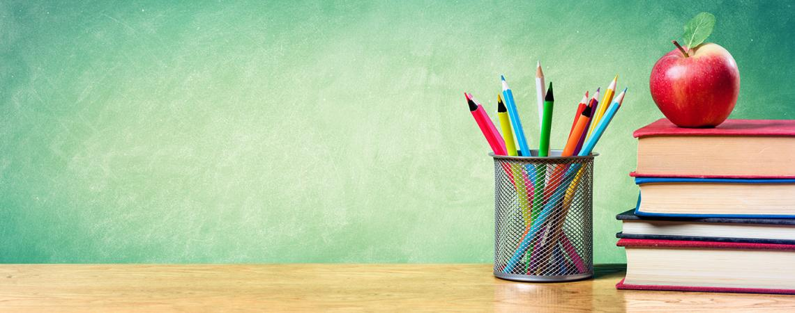 Photo of books, an apple, and a pencil holder with pencils.