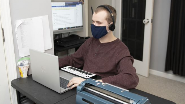 Dylan working on computer with mask