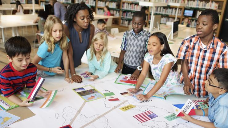 Group of diverse students around a table with their teacher learning about countries.