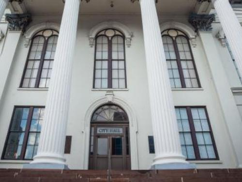 exterior of white courthouse with tall columns and arched door