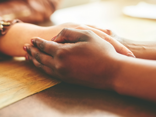 Two people holding hands across a table comforting one another