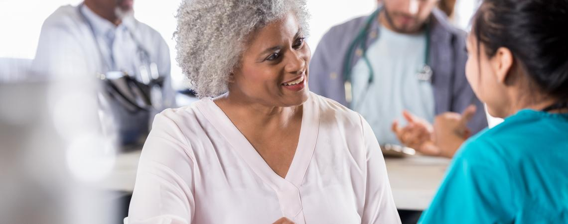Elderly woman talking with a health professional