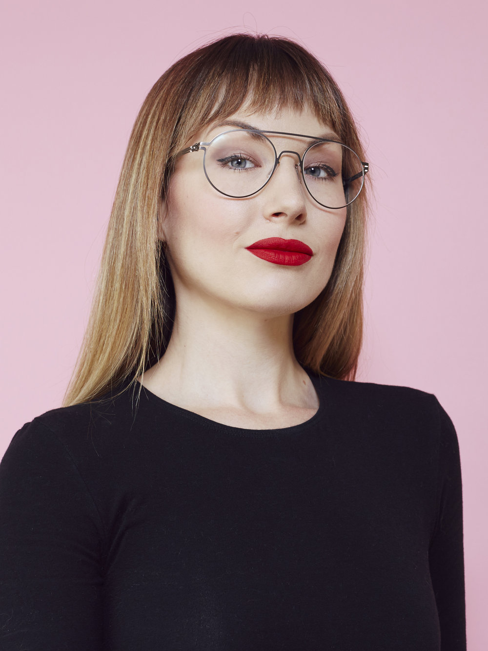 Woman with bangs, glasses and red lipstick in black shirt posing in front of pink background