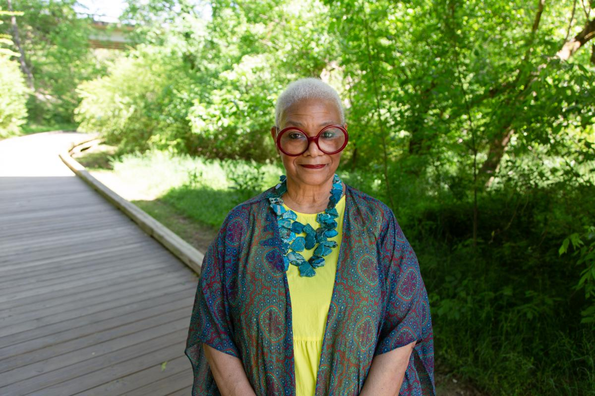 Jaki Shelton Green standing on a wooden walkway with greenery behind her