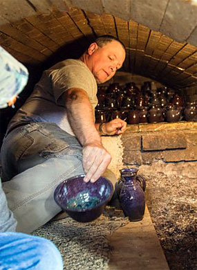 Pottery being retrieved from a kiln at the Annual Heritage Day and Wood Kiln