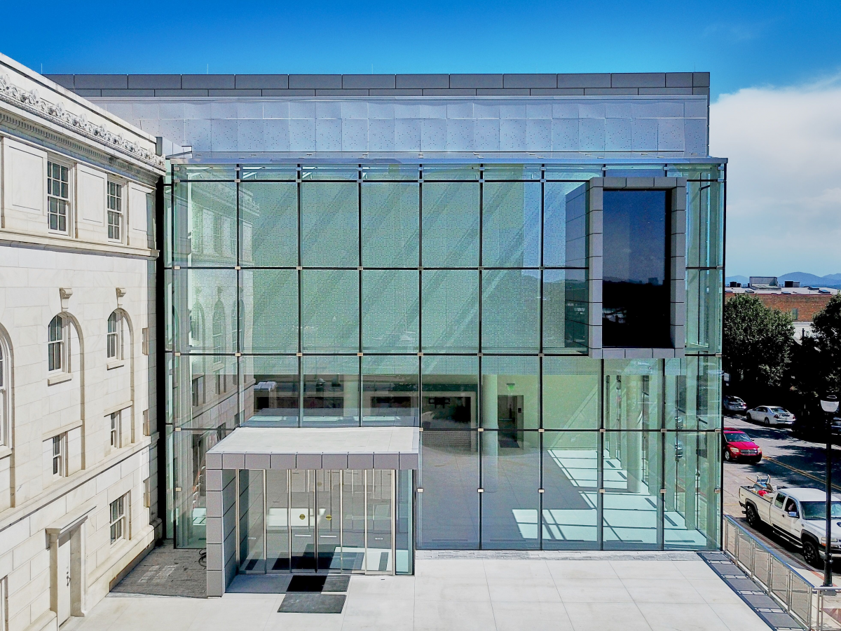 A photo of a building with a large wall of glass windows.