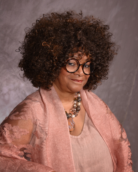 A photograph of Jaki Shelton Green, a Black woman with a curly afro, big round glasses, and
