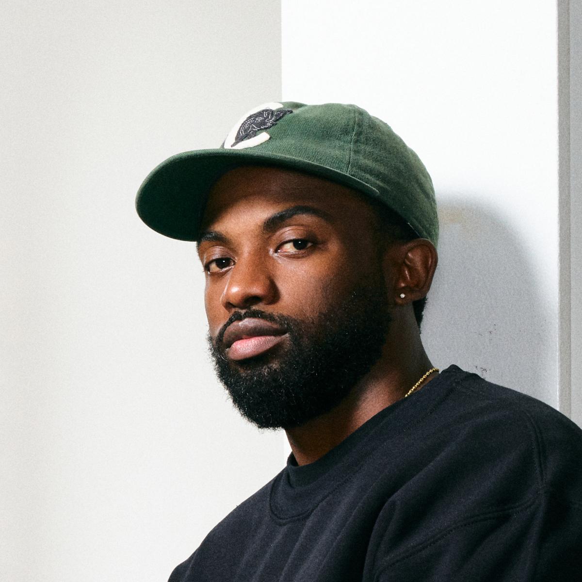 Photograph of a Black man- Sherrill Roland- with a beard wearing a dark sweatshirt and a green baseball cap.