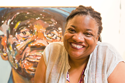 Photo of woman smiling with painting in background