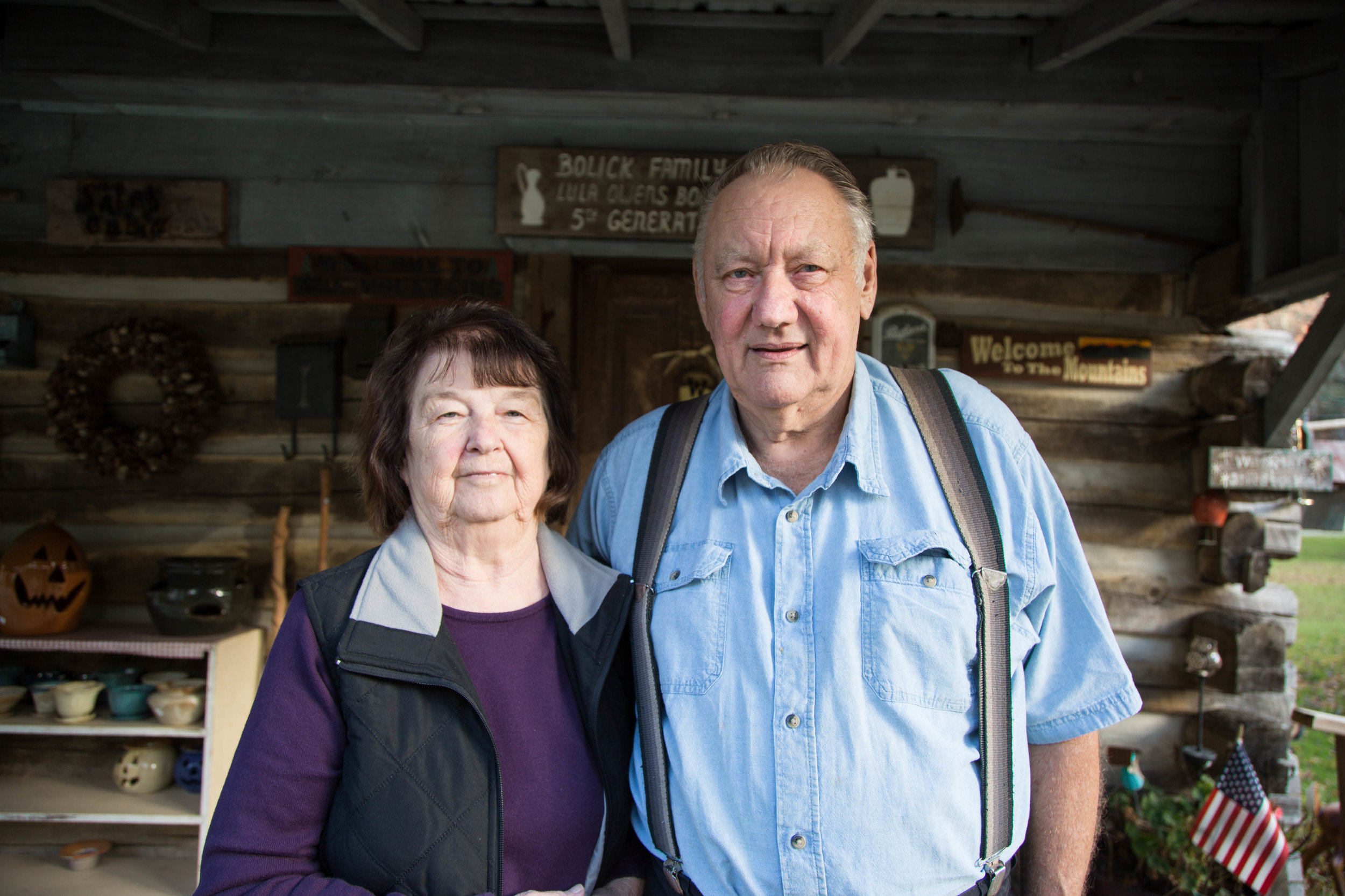 Man and woman standing outside in front of pottery studio.