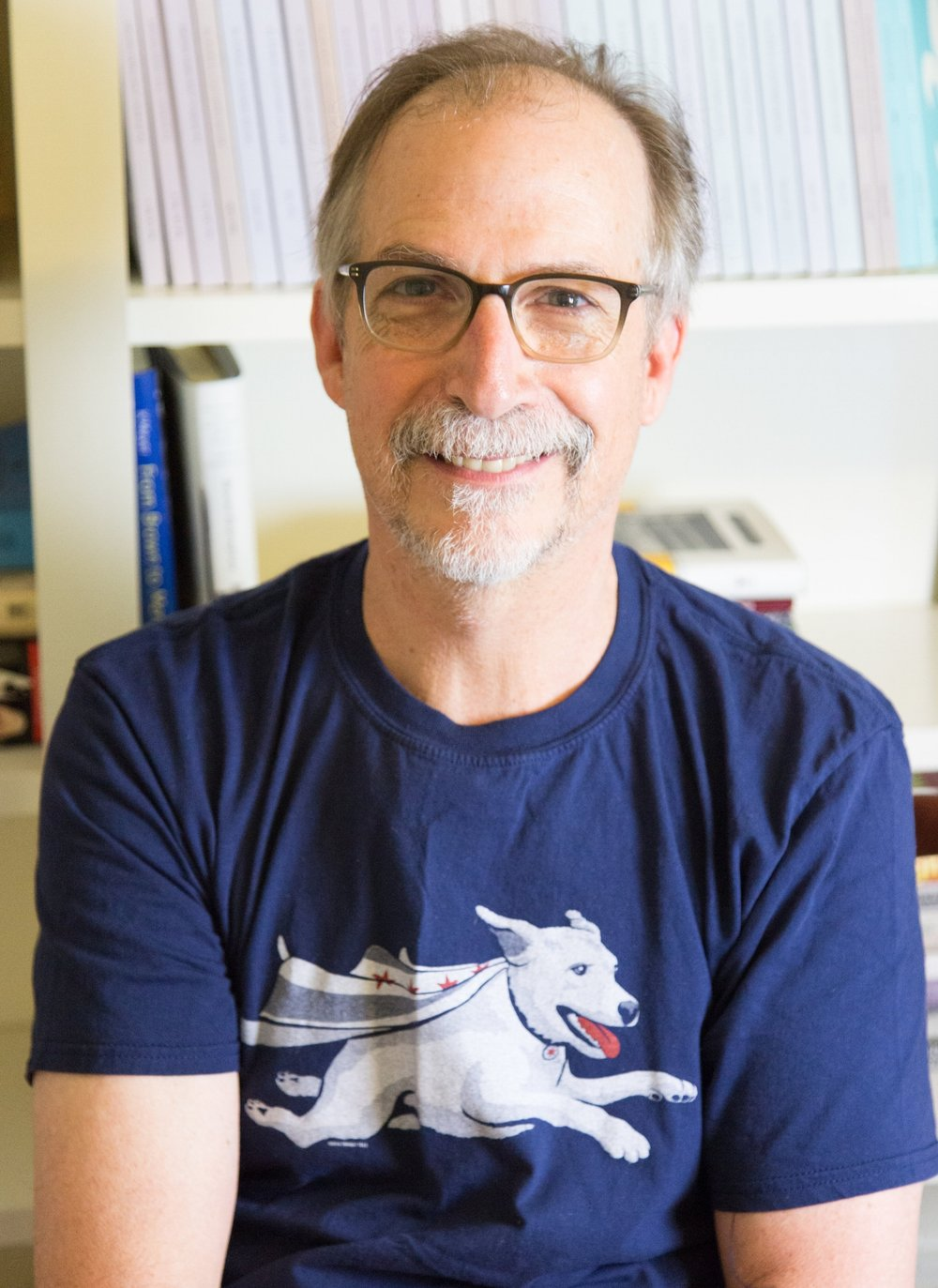 Man with glasses, goatee and blue t-shirt with a dog on it