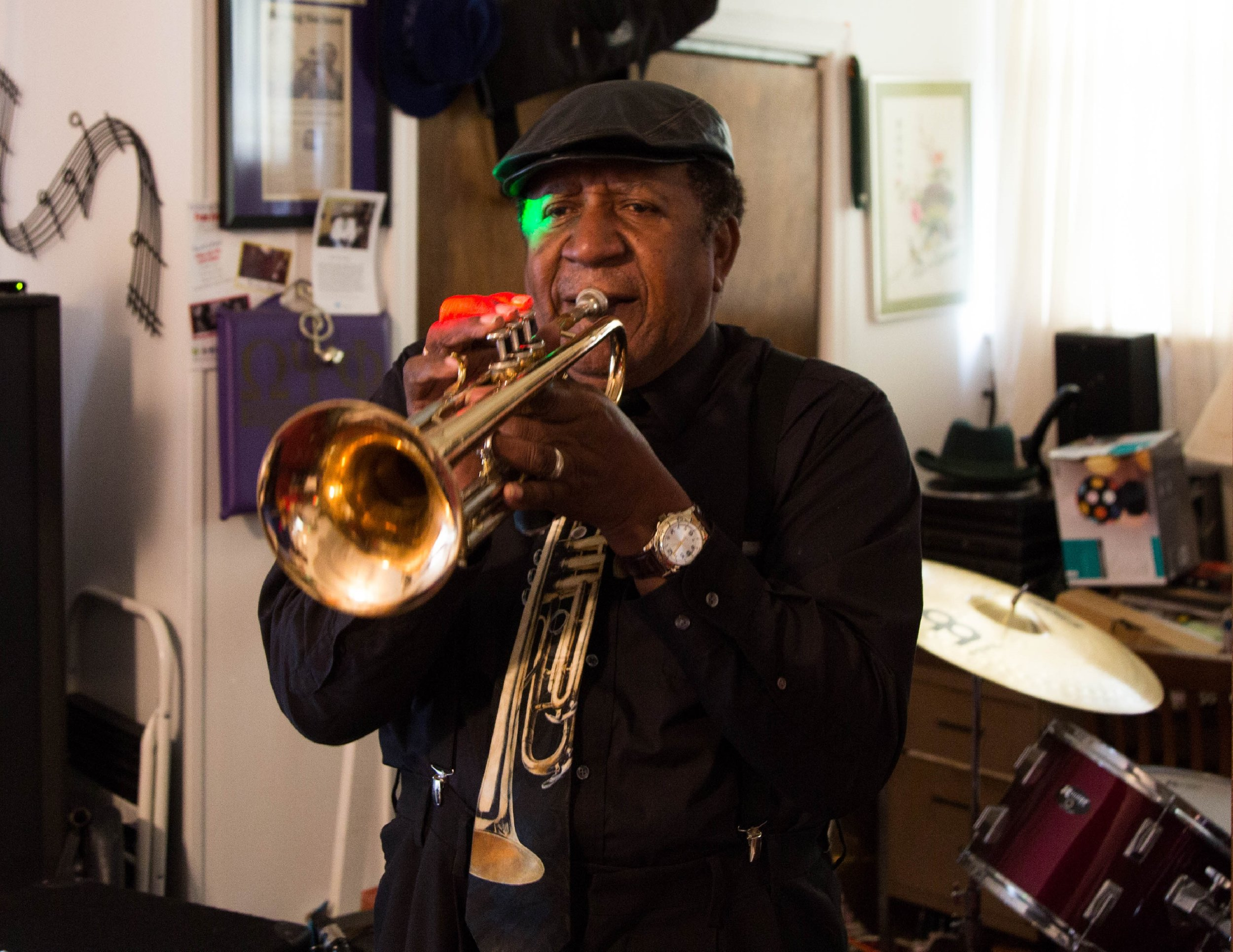 Man in all black and hat playing trumpet