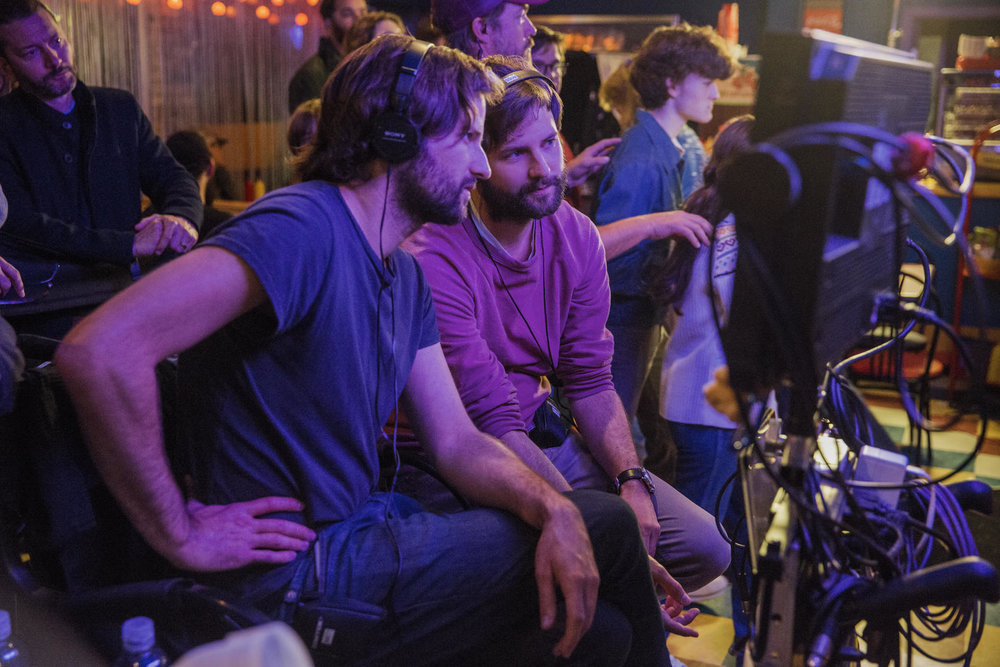 Two people with headsets looking at screen with other people in background