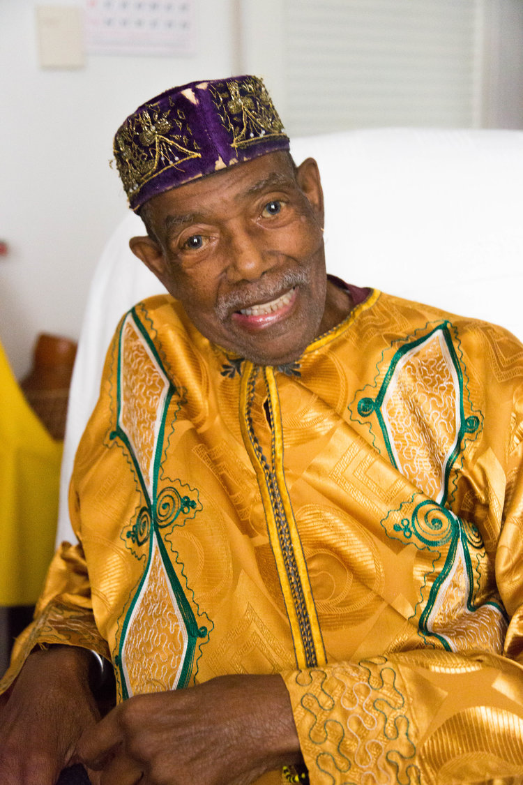 Older black man in yellow outfit and purple hat