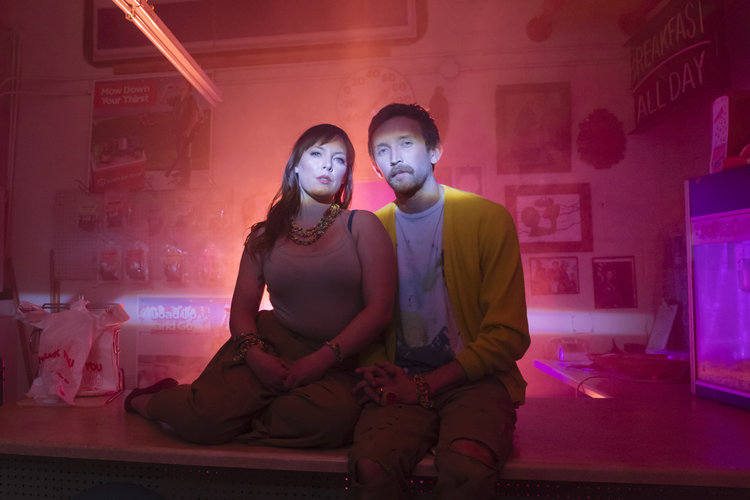 Two people sitting on a counter with red and purple lights around them