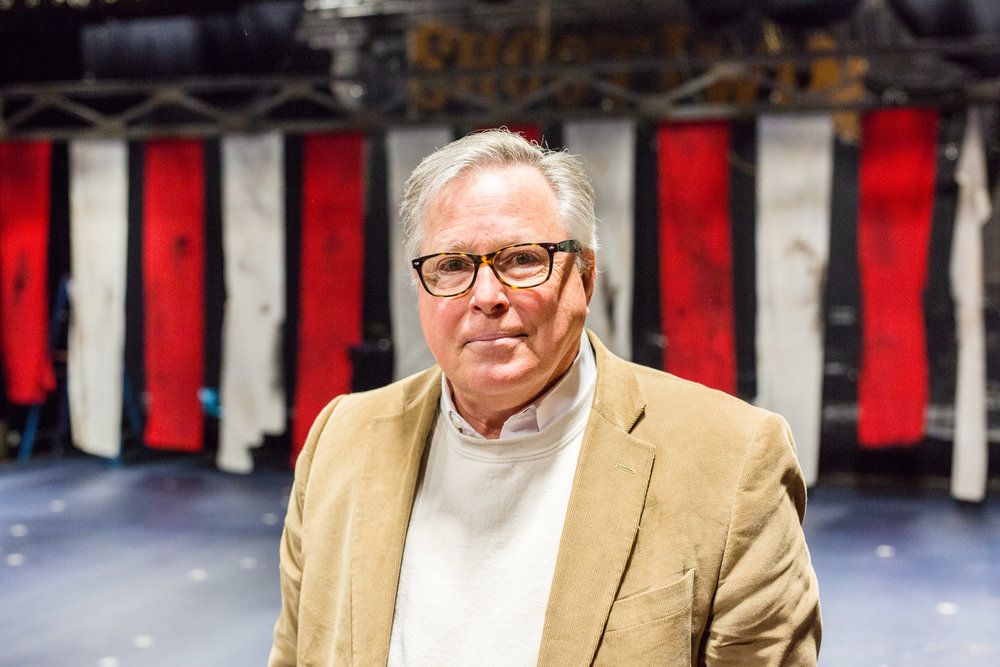 Headshot of man in blazer and glasses smiling with theatre rigging in background