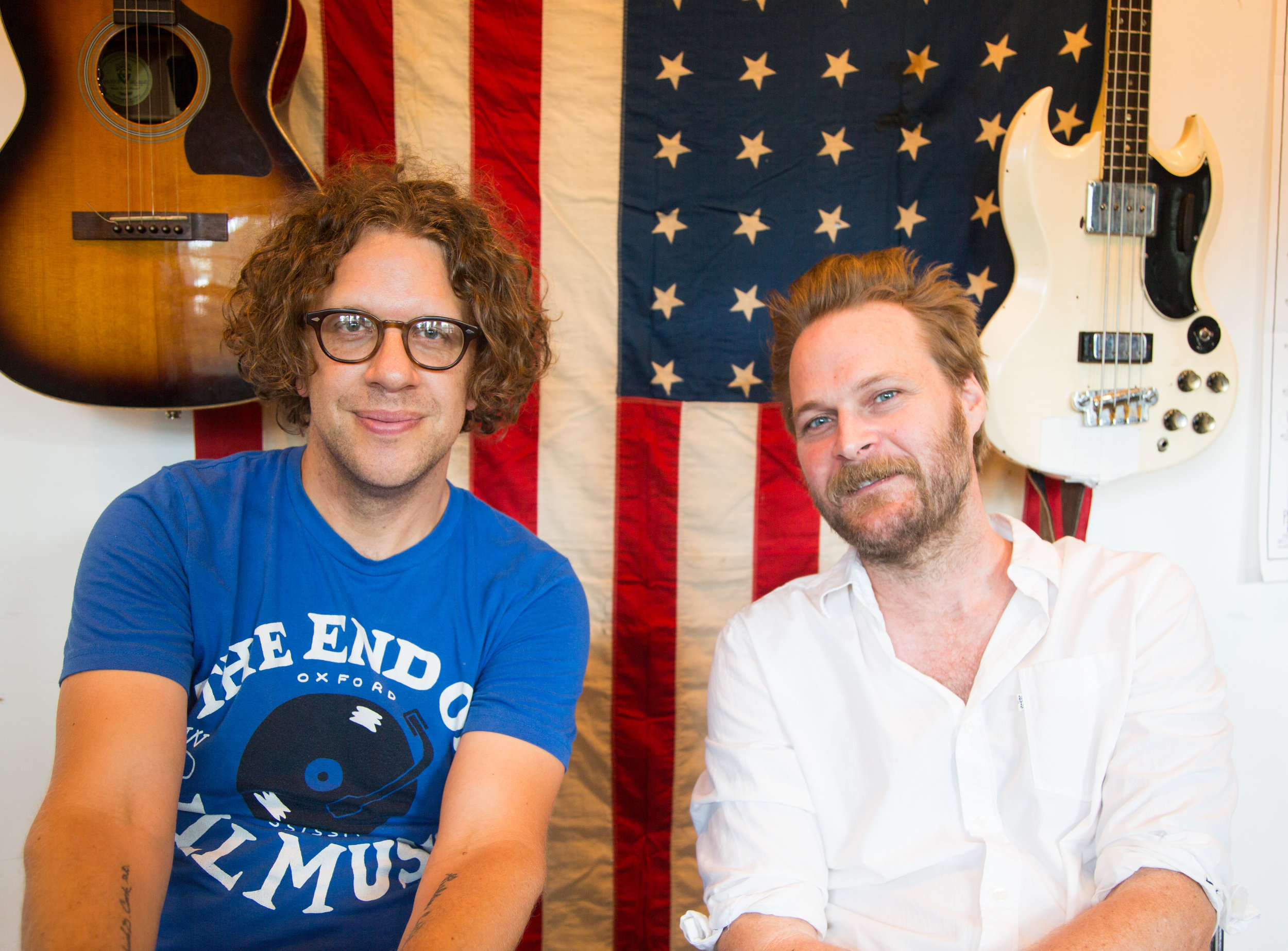 Two men in front of American flag and two guitars
