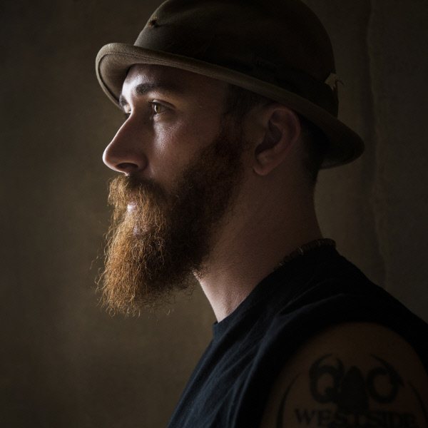 Man with beard and hat, headshot from side angle