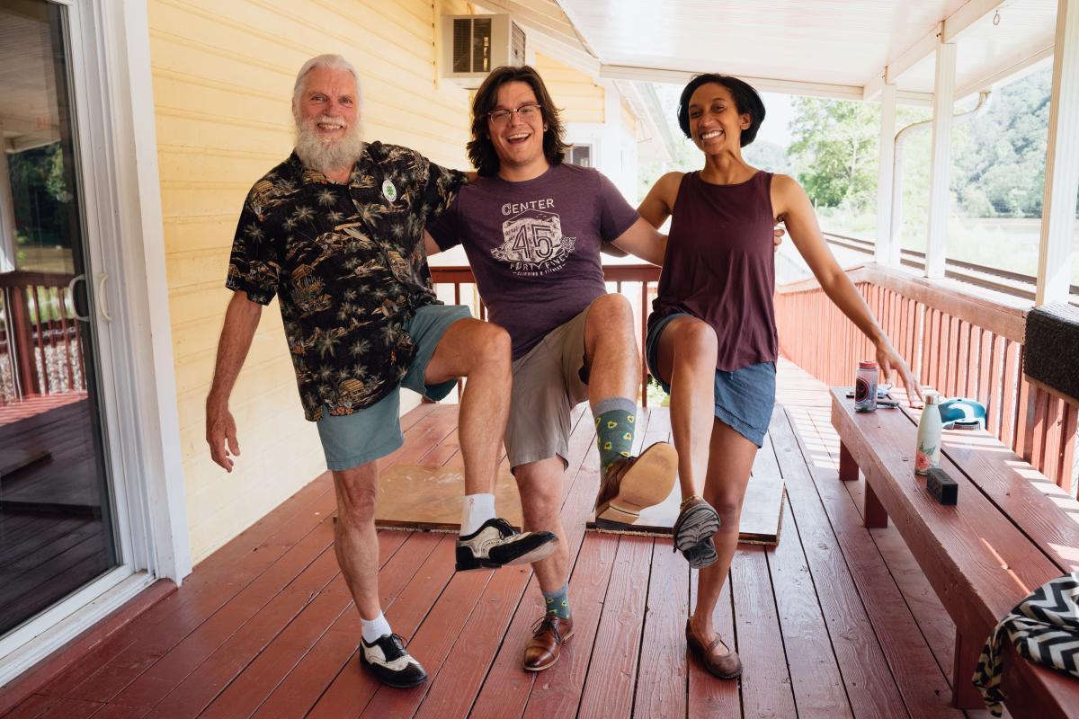 Rodney Sutton, Willard Watson, and Melissa Edd dancing on a porch