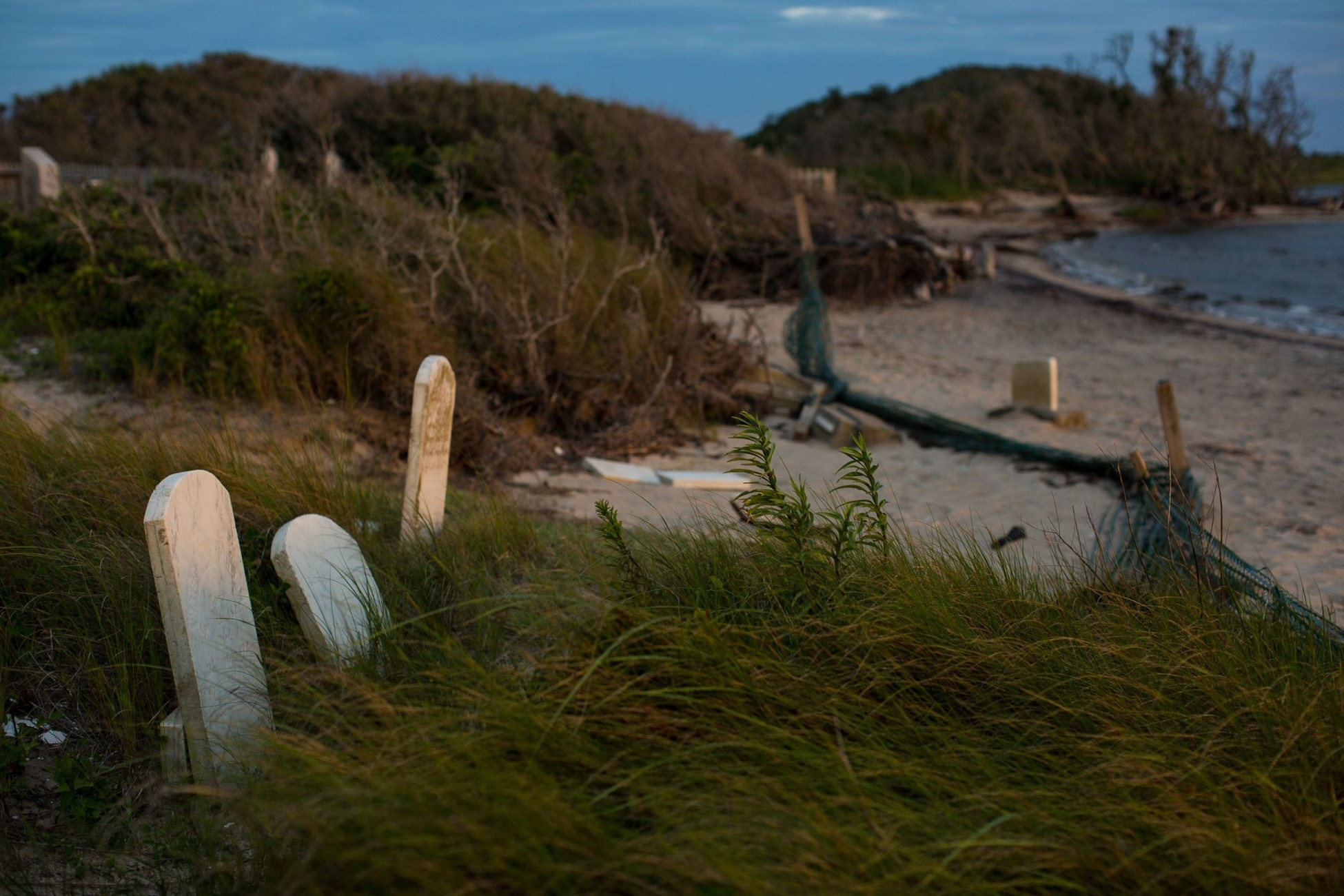 Several old headstones in a community center sit several yards from the shoreline of the Pamlico Sound.