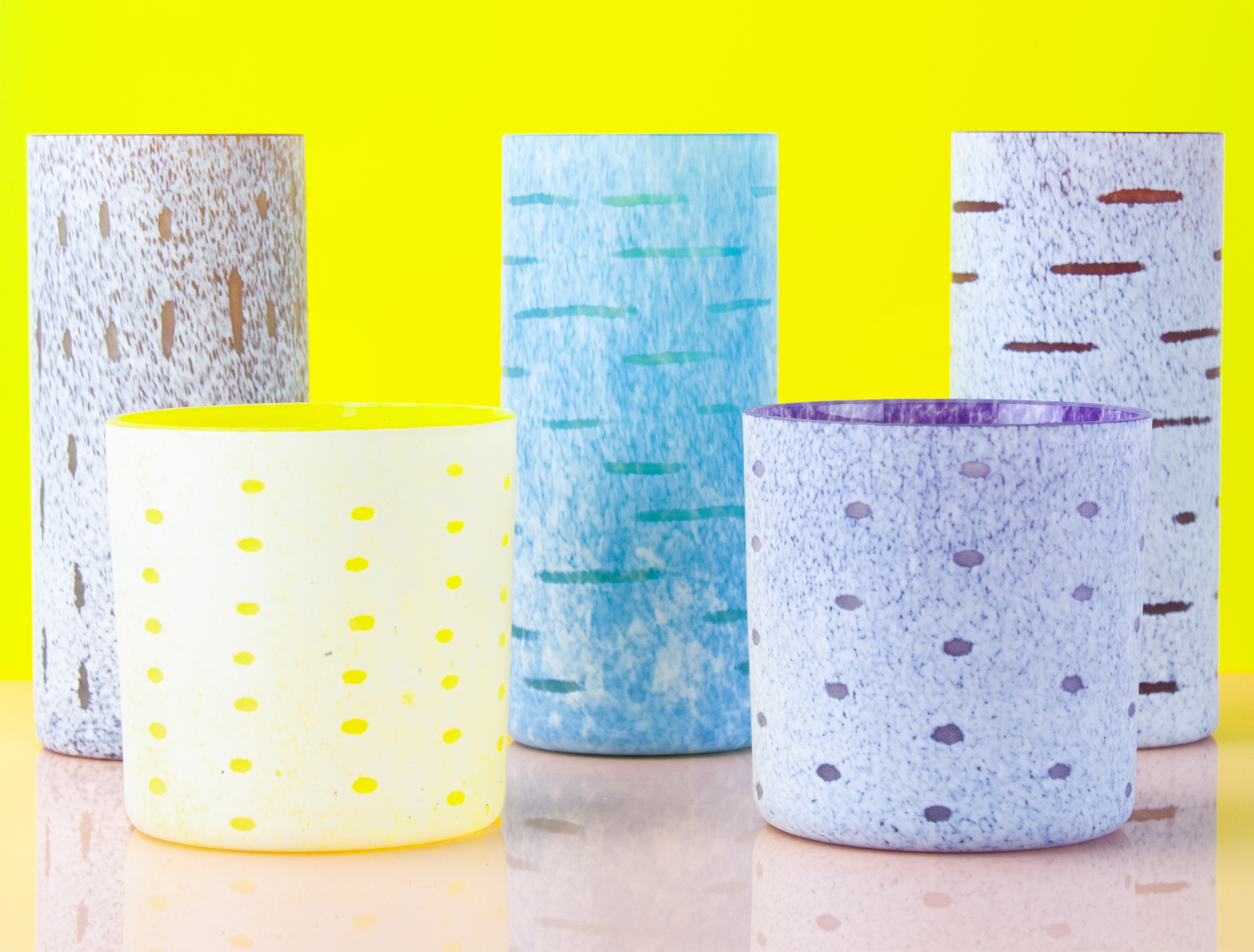 Five brightly colored glass cups, two small, two tall, in front of a bright yellow background.