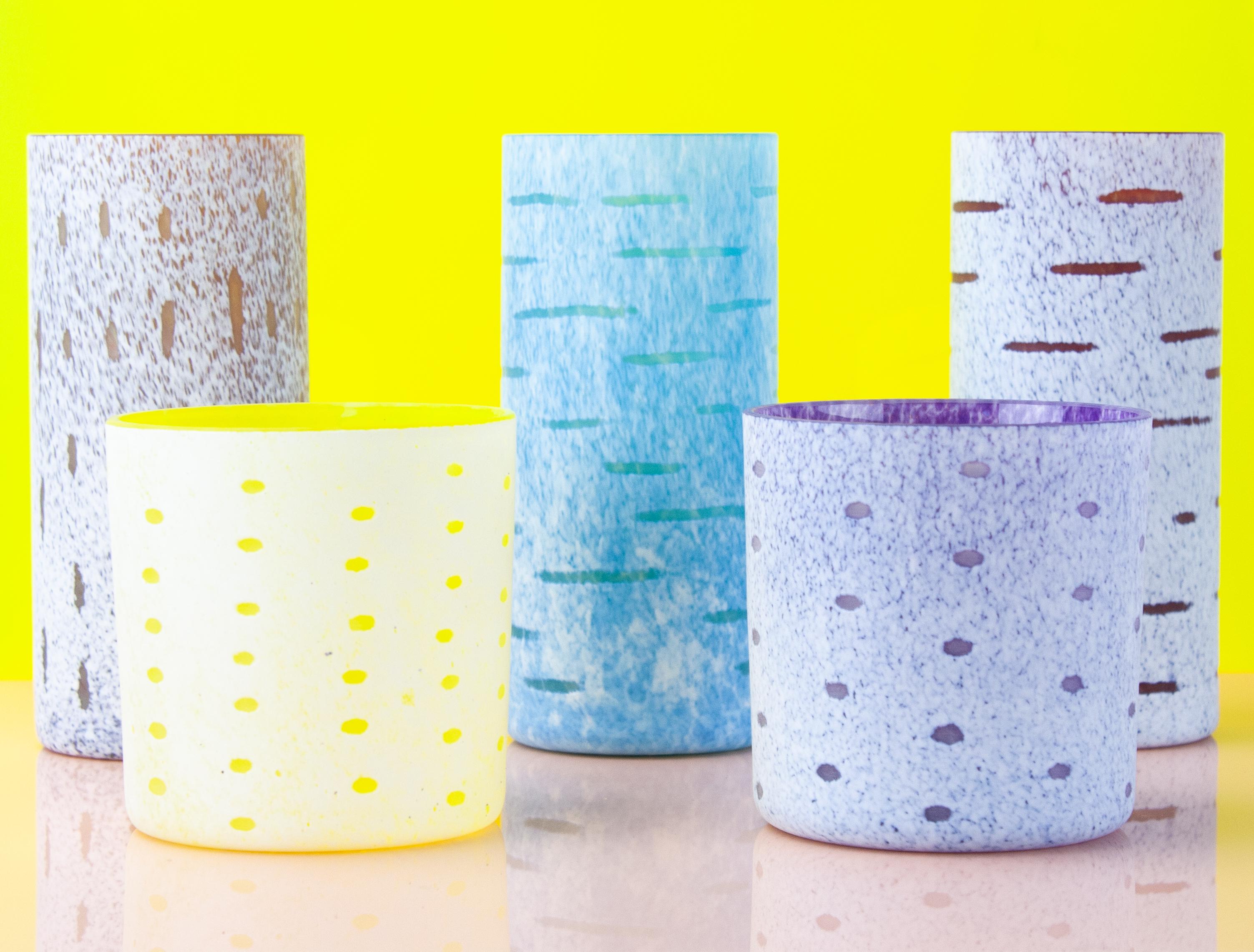 五个色彩鲜艳的玻璃杯子,两个小的,两个高的,前面是明黄色的背景.