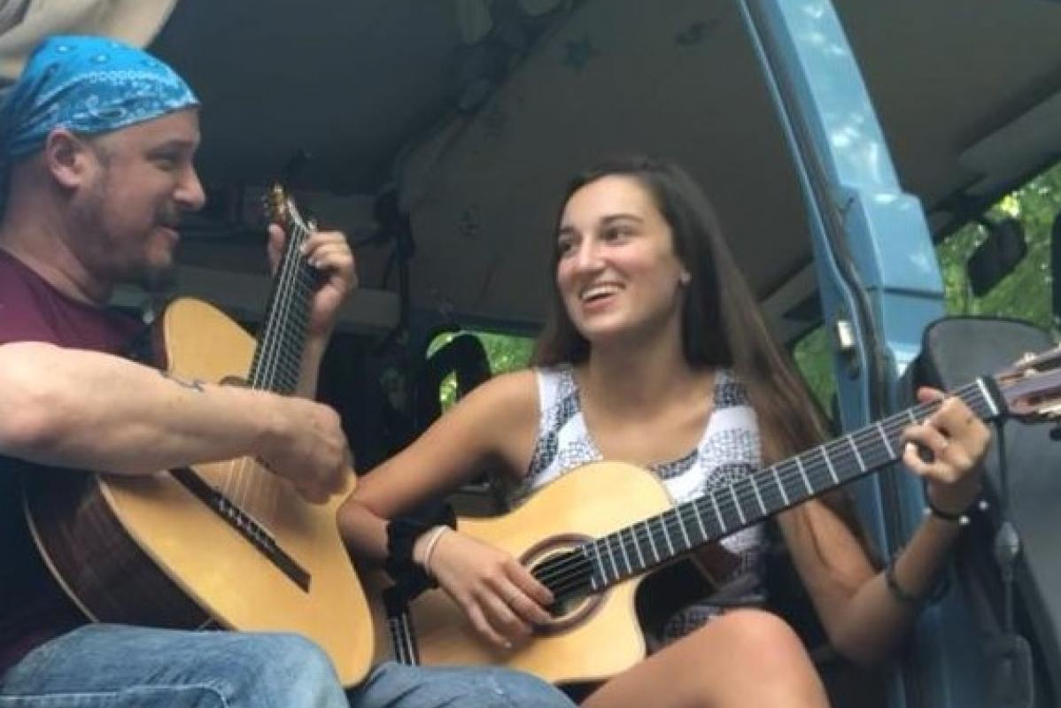 Luis Del Río playing guitar with his daughter Mia