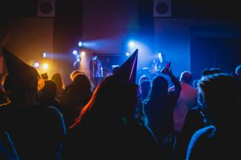 audience with party hats in a darken room listening to a performer on stage