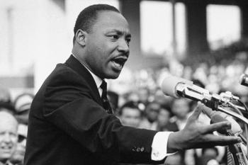 A black and white photo of Martin Luther King Jr. speaking in front of a crowd