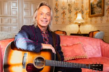 Jim Lauderdale seated with a guitar at the Governor's mansion