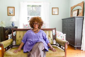 A photograph of Jaki Shelton Green wearing a purple blouse sitting on a green couch