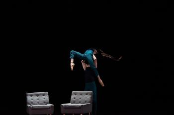 两把椅子,一个舞者把另一个舞者举到空中