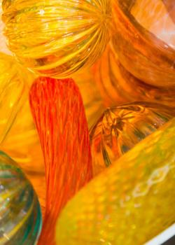 A close-up photo of various glass ornaments in yellow, orange, and green.