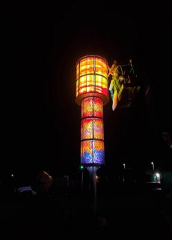 A photograph at night of a lit up tower filled with glass ornaments in red, orange, yellow, and blue.