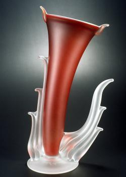 A photo of a red glass vessel with clear glass waves coming off the sides.