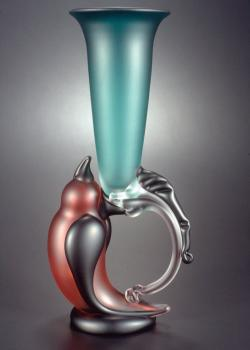 A photo of a red and blue glass goblet; the base is formed with a bird.