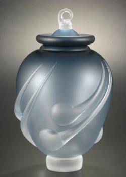 A photo of a light blue glass urn with a lid.