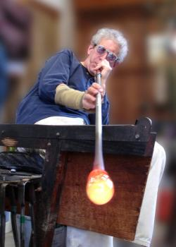 A man blowing into a long metal pipe with hot orange glowing glass at the end.