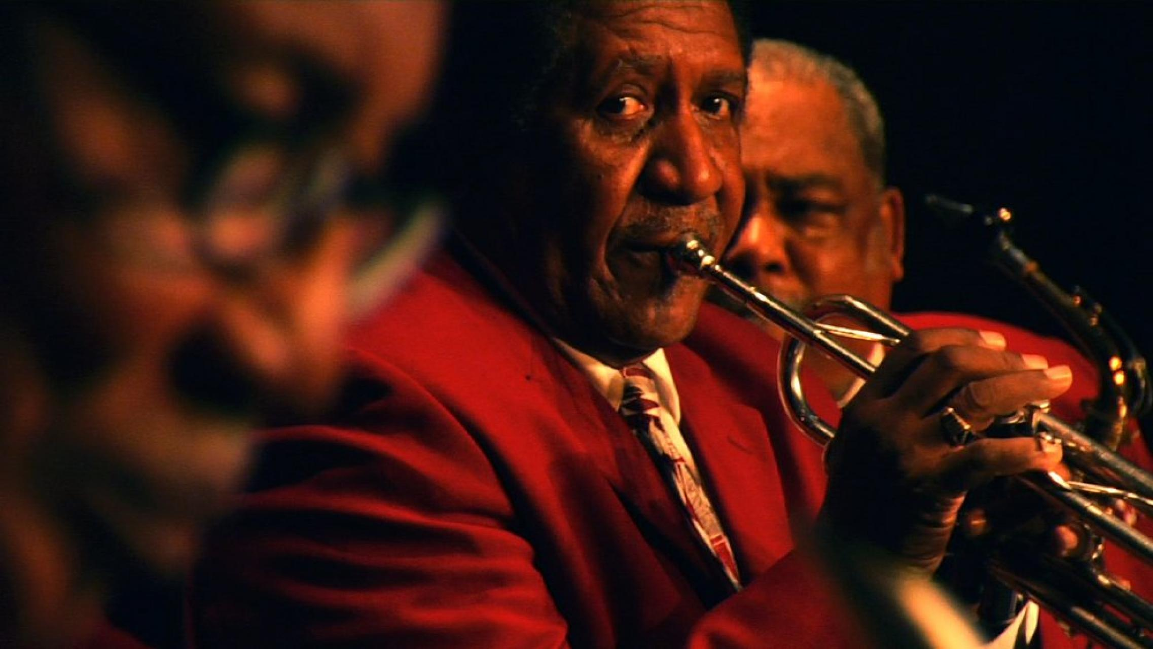 Close up of man in red suit playing trumpet.