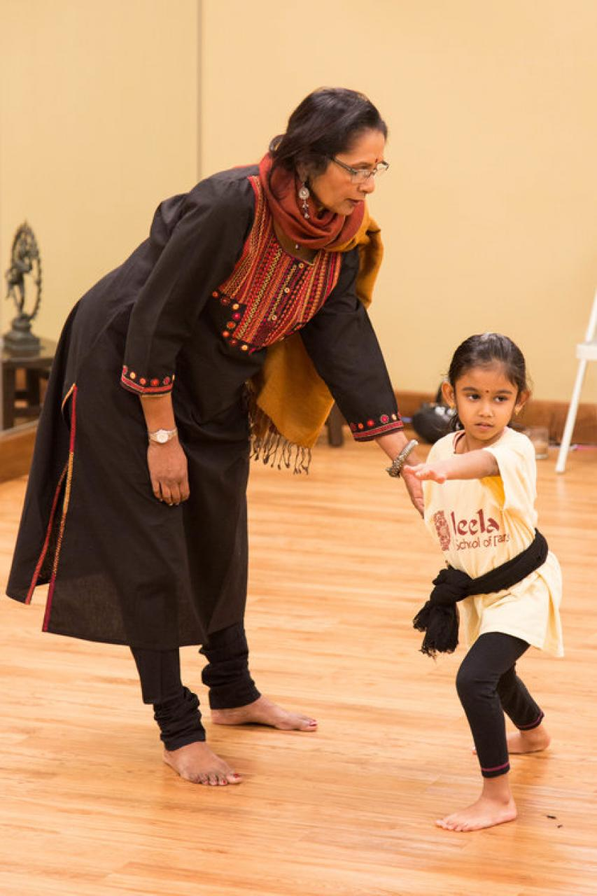 Woman, standing, leaning over to assist young girl dancing.