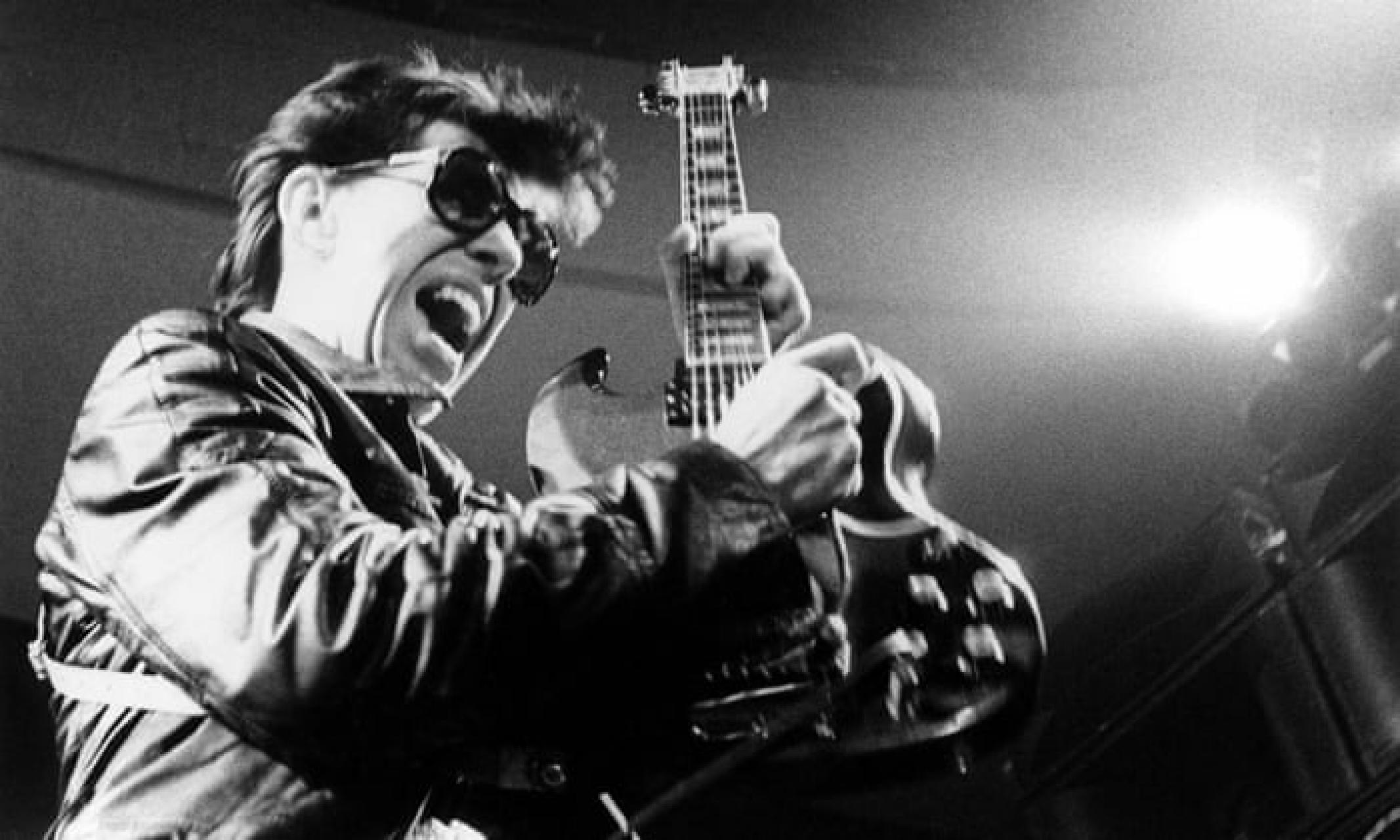 Link Wray holding his guitar, scowling