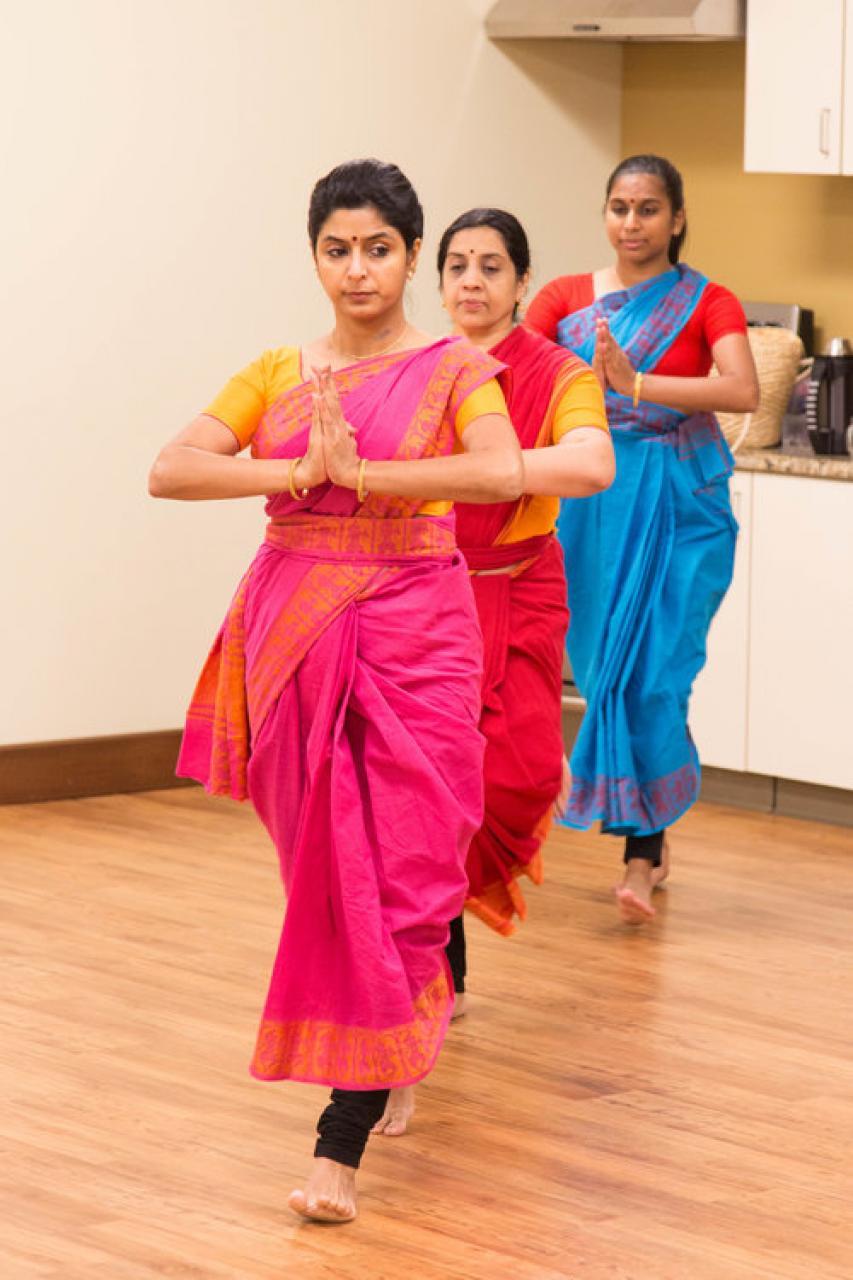 Three women walking, with hands in prayer shape, in costume.