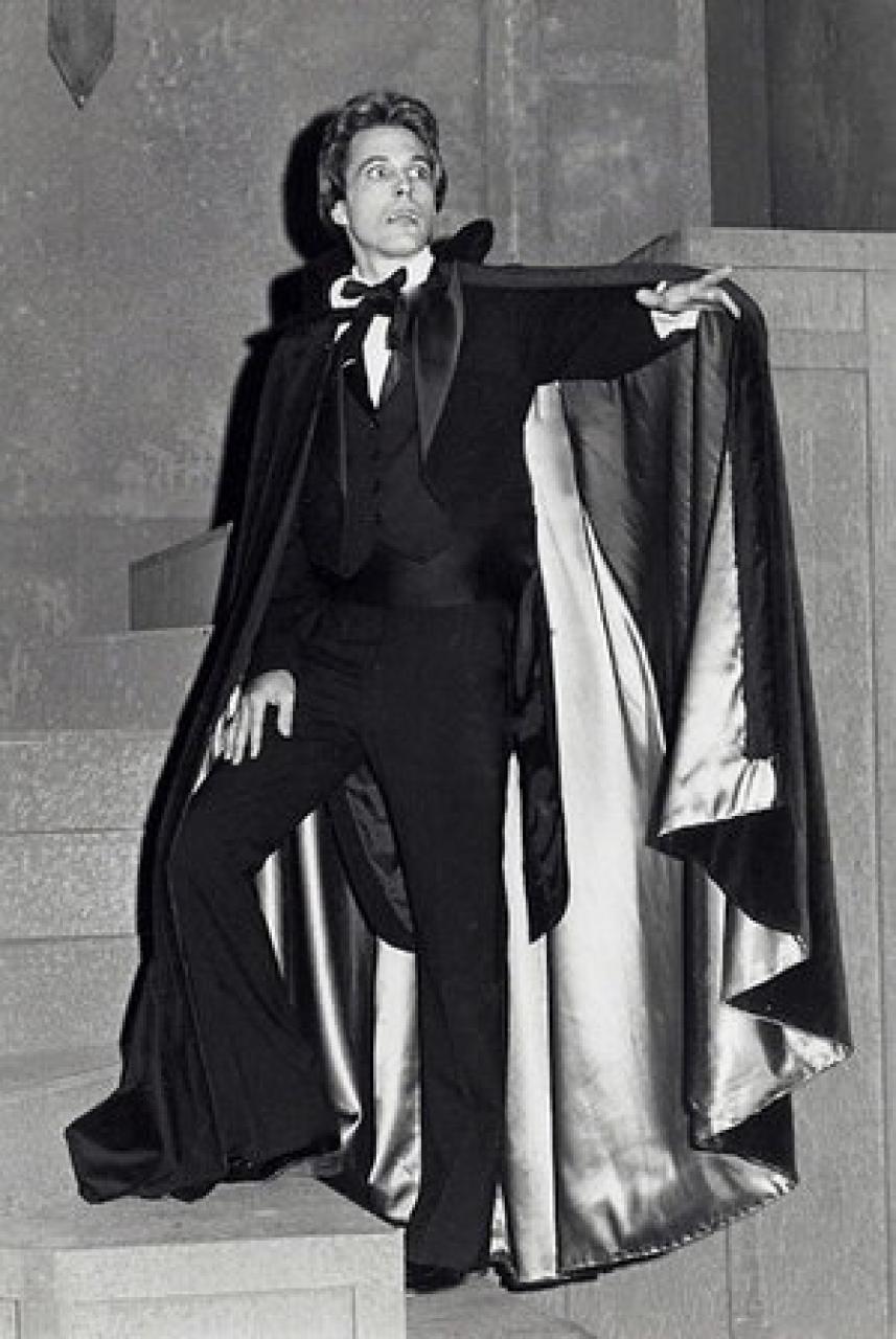 B&W photo of a man in custom, acting.