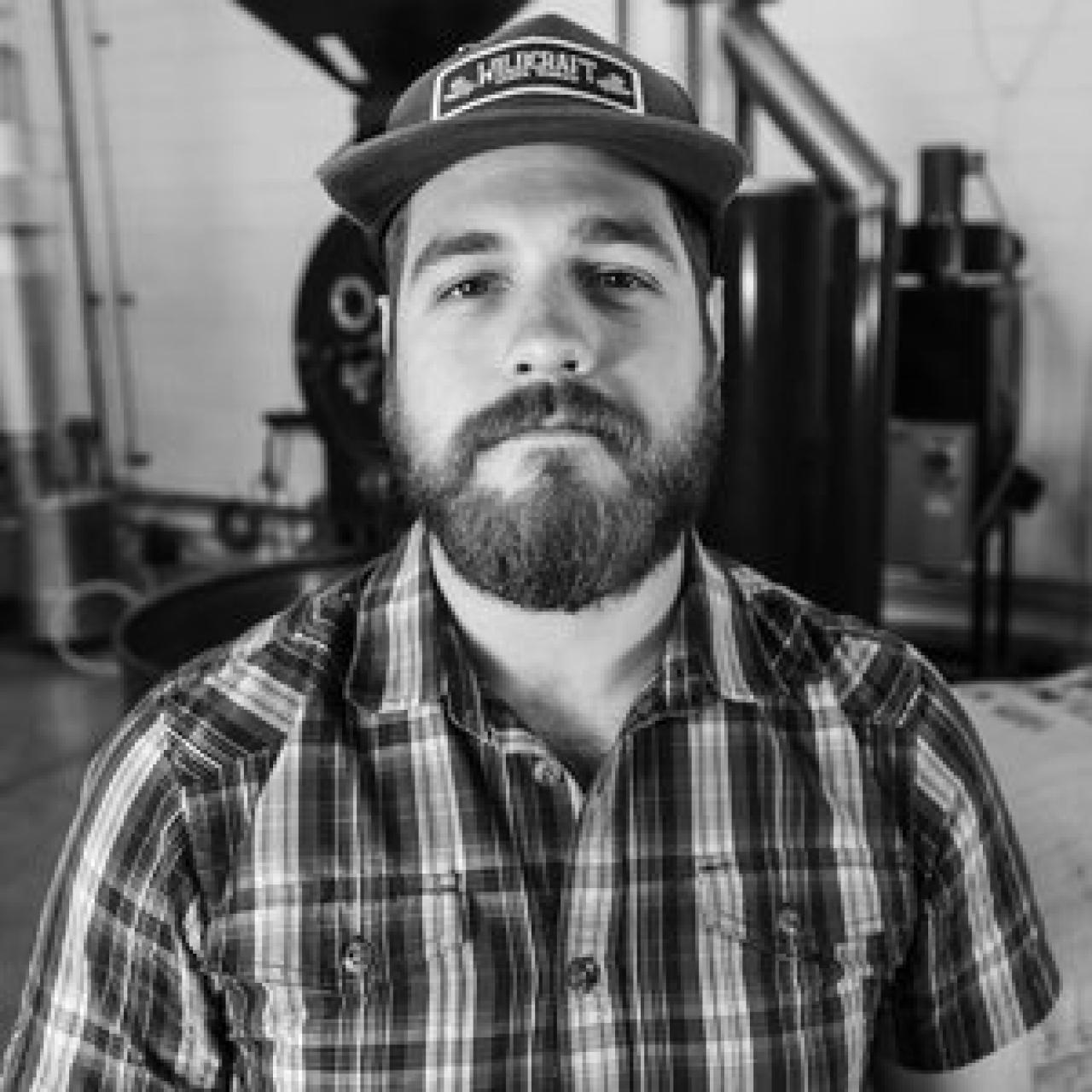 B&W headshot of a man with a beard wearing a cap and plaid shirt.